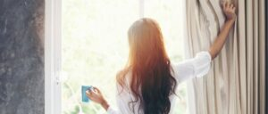 Woman waking up, opening her curtains, starting the daily habits for her self-care morning routine
