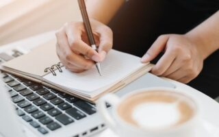 Woman writing down daily positive affirmations