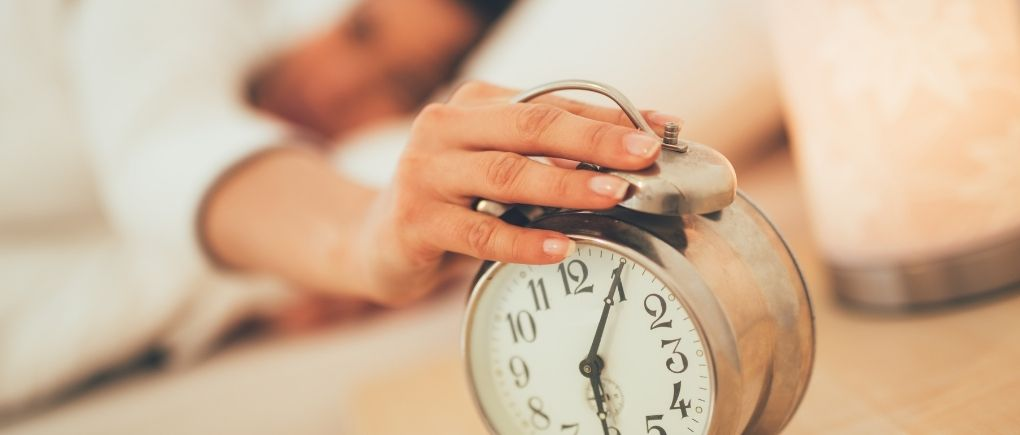 Woman waking up pressing the snooze button