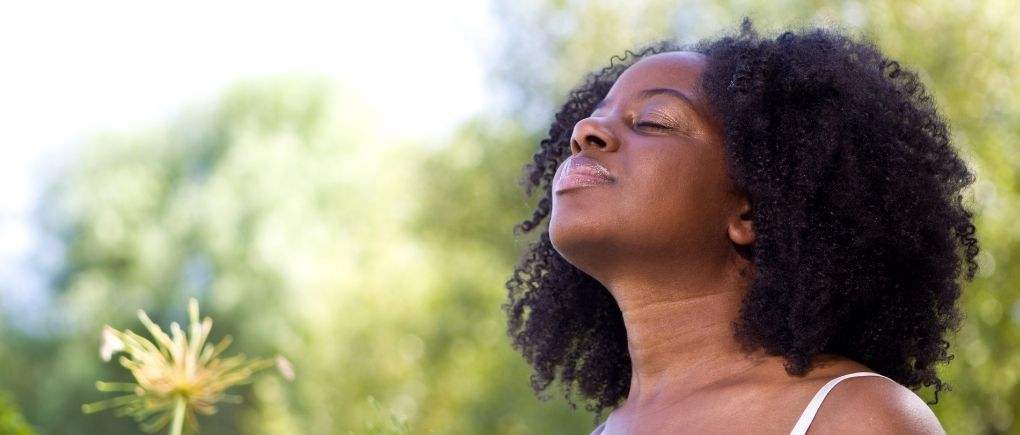 A black woman feeling calm and at peace, smiling and she is outside