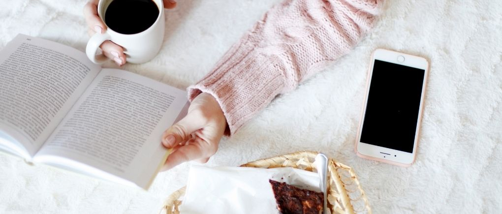 A woman reading a book for her perfect morning routine