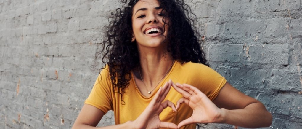 A woman in a yellow t-shirt making a heart with her hands